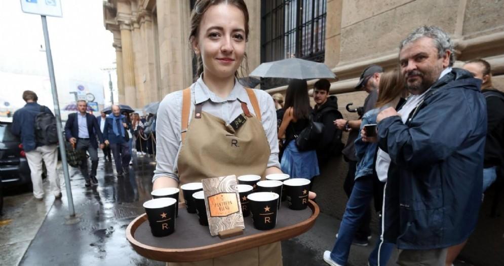 Una addetta di Starbucks offre caffè ai clienti in coda per accedere alla caffetteria americana aperta in piazza Cordusio a Milano