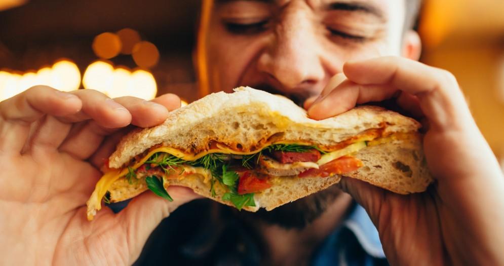 Uomo che mangia un panino - Immagine di repertorio