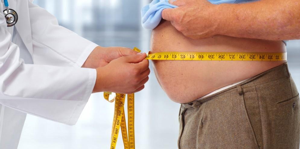 Un dottore mentre misura la circonferenza vita