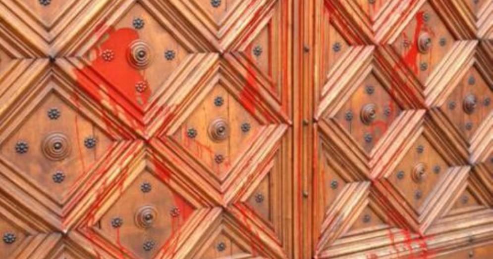 Il portone del Duomo di Pinerolo imbrattato da attivisti «no border»