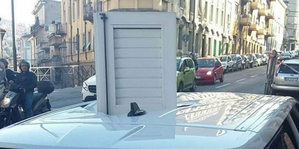 Scuretto di una finestra sfonda il tettuccio di un'auto in sosta