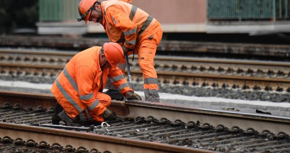 Operai al lavoro per ripristinare la linea ferroviaria danneggiata da un carro merci