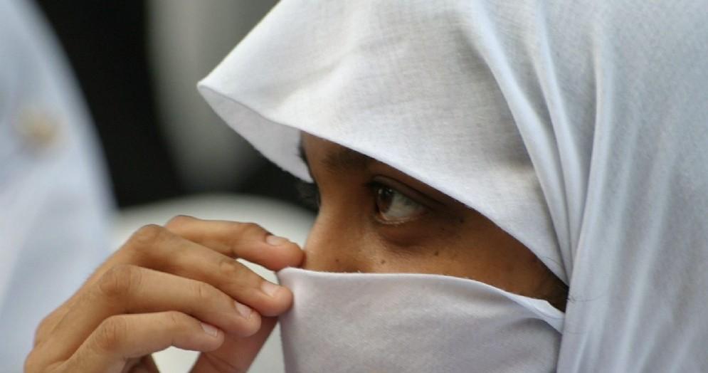 Una ragazza musulmana si copre il volto con il velo