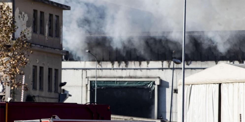 Vigili del fuoco al lavoro per il vasto incendio divampato in un capannone adibito a deposito rifiuti nell'impianto Ama di via Salaria, Roma,