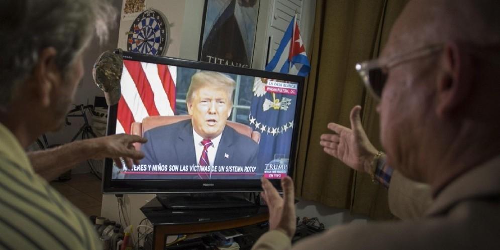 Una coppia di americani guarda in tv il presidente Donald Trump durante il suo discorso sull'immigrazione dallo Studio Ovale
