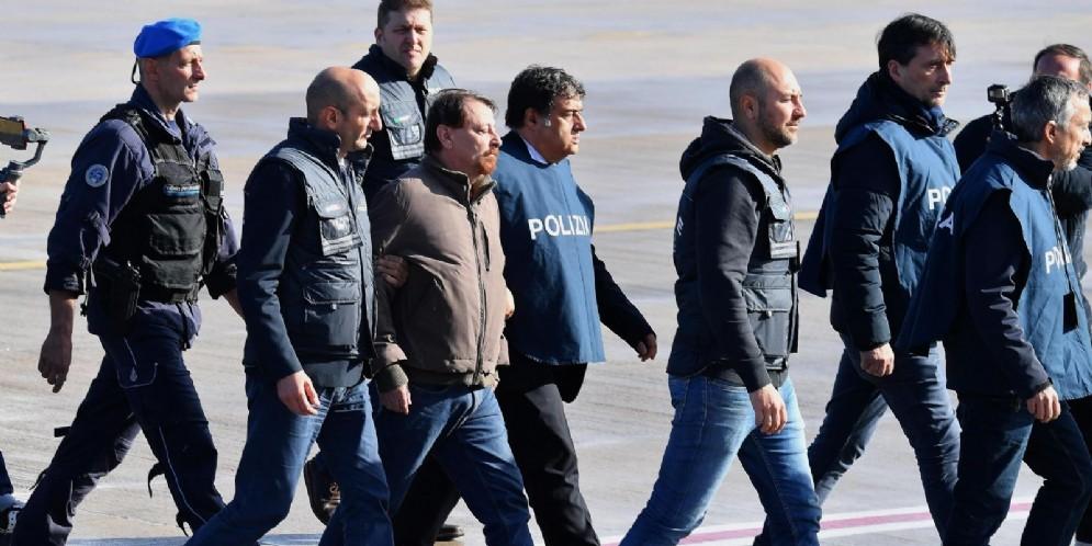 Cesare Battisti mentre atterra all'aeroporto di Ciampino scortato dagli agenti della Polizia