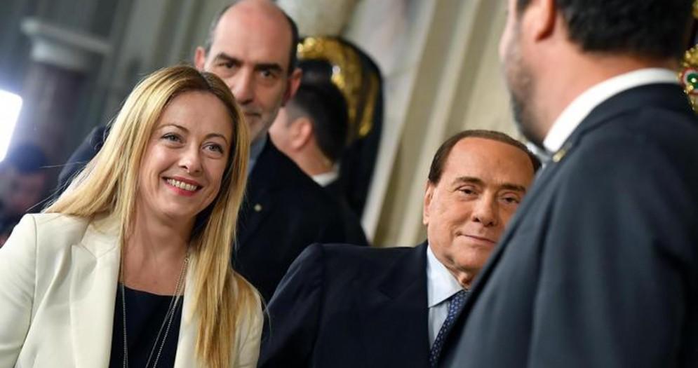 Giorgia Meloni, Silvio Berlusconi e Matteo Salvini (di spalle)