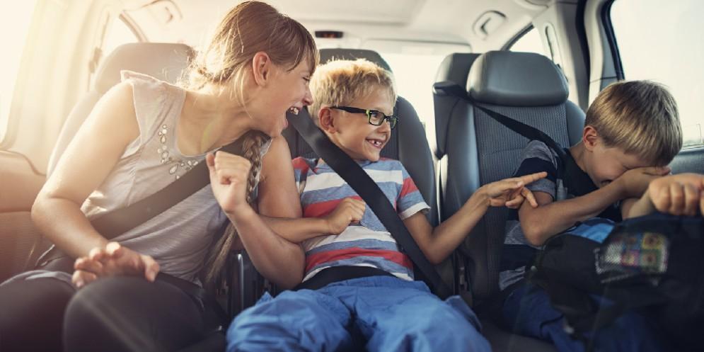 Mamma e bambini che si divertono in macchina durante un viaggio