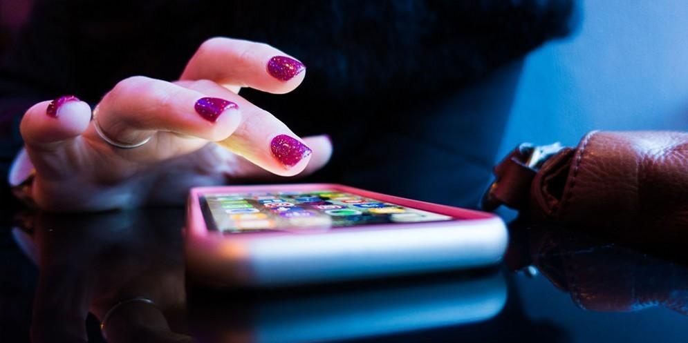 Una mano femminile con lo smartphone