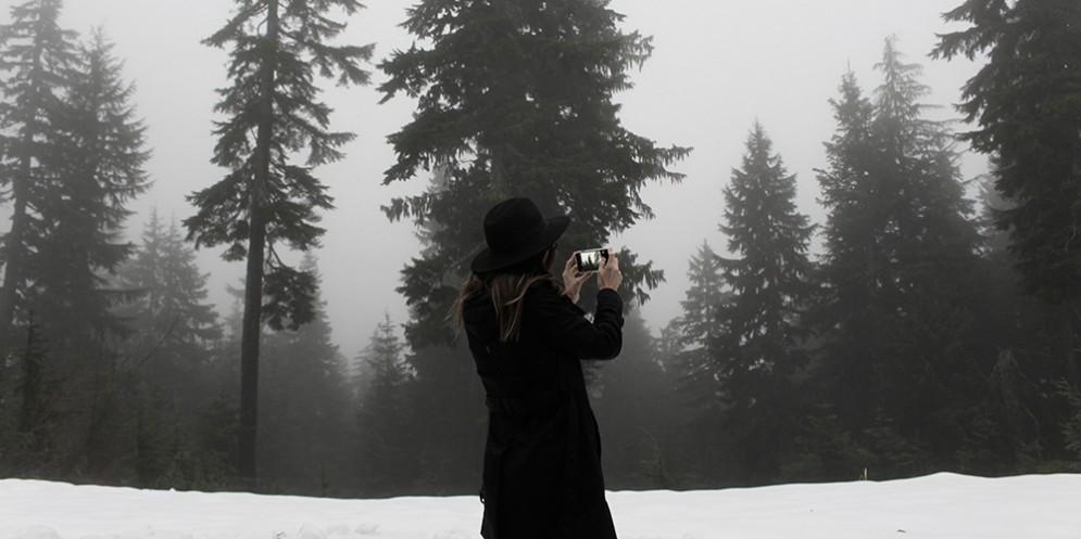 Una ragazza fotografa un paesaggio innevato