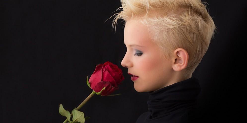Una giovane ragazza che annusa una rosa
