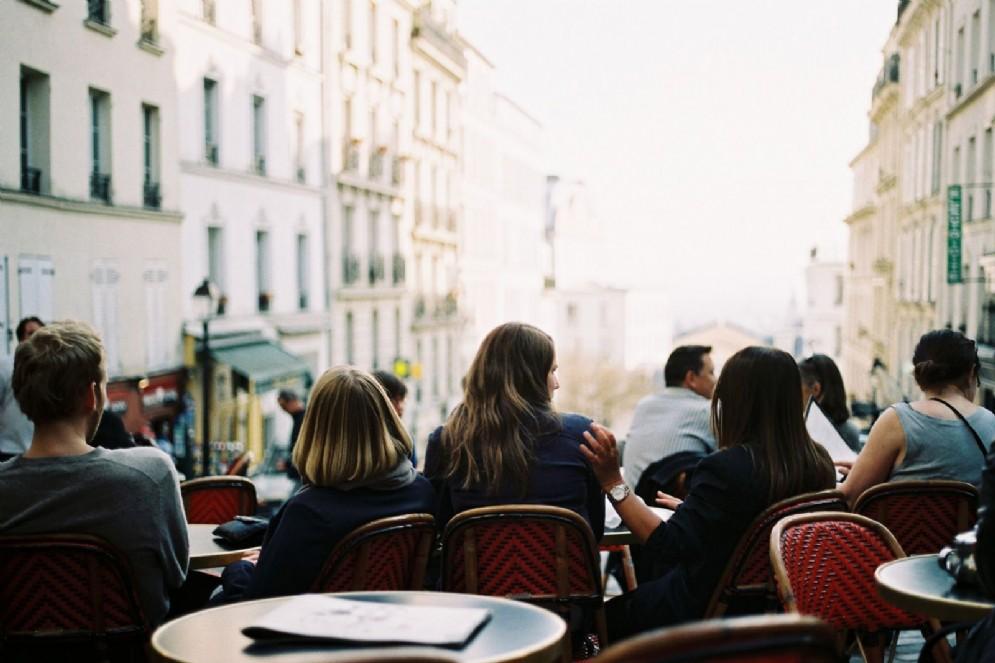 Persone sedute ai tavolini di un bar