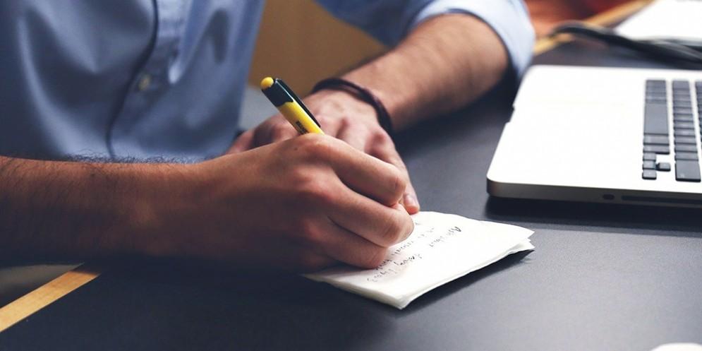 Uomo con penna e laptot per analizzare mutui online