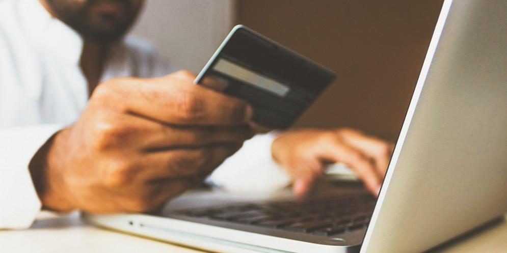 Una persona con la carta di credito al portatile