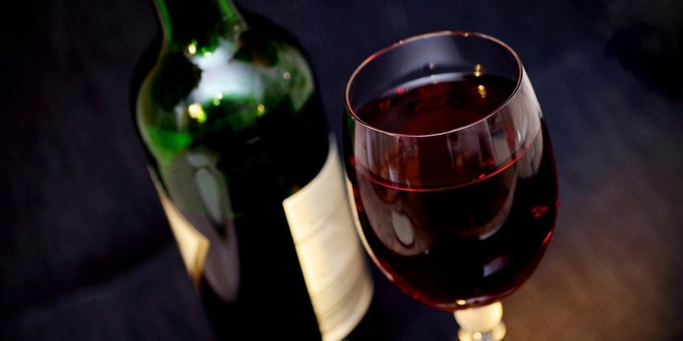 Una bottiglia con un calice di vino rosso