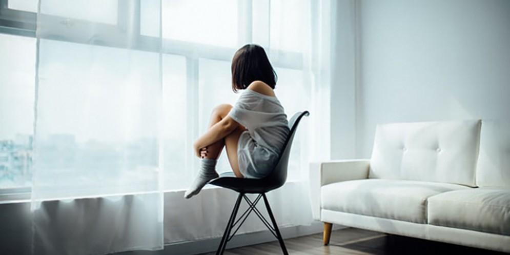 Una giovane ragazza in una stanza seduta su una sedia